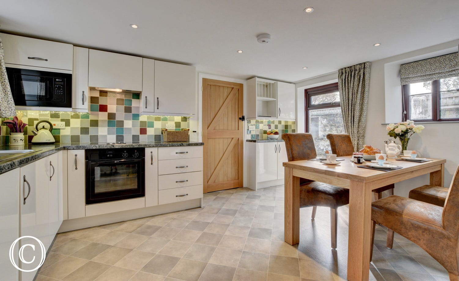 The well equipped kitchen with an attractive dining area overlooks the courtyard