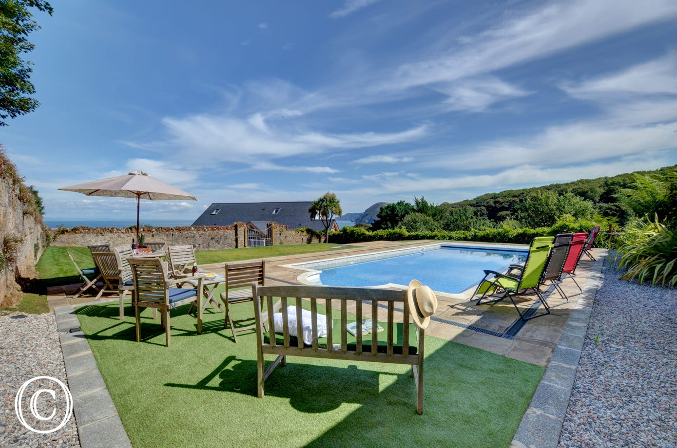 The beautiful swimming pool area with garden furniture