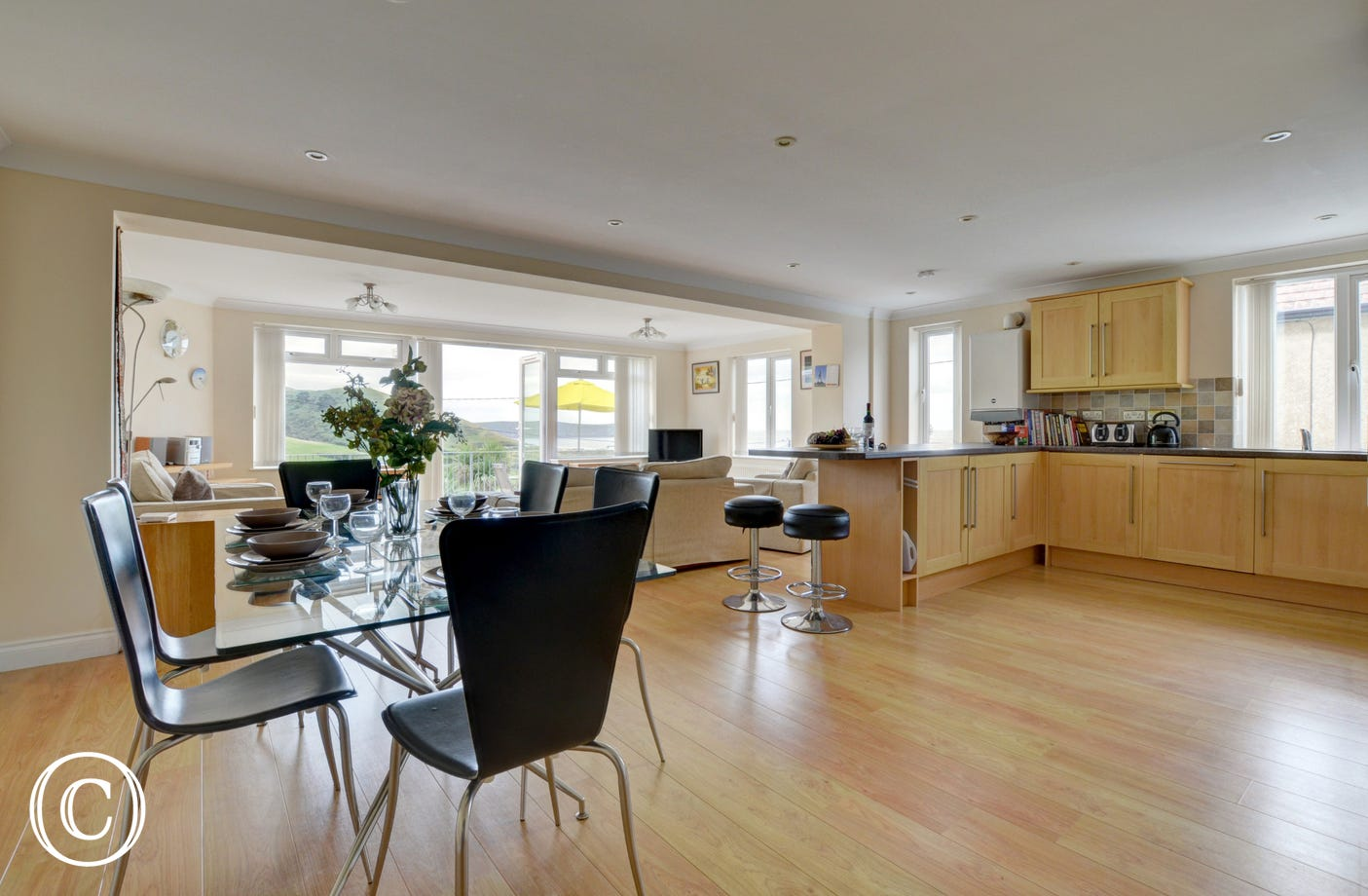Very spacious open plan living room with stylish kitchen and dining areas complemented by wooden flooring