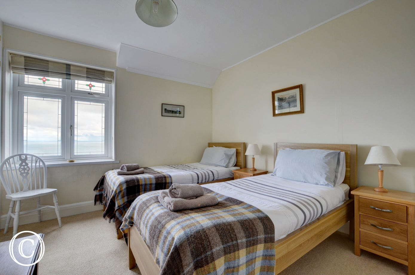 This delightful twin bedroom offers views of the surrounding countryside and out to sea