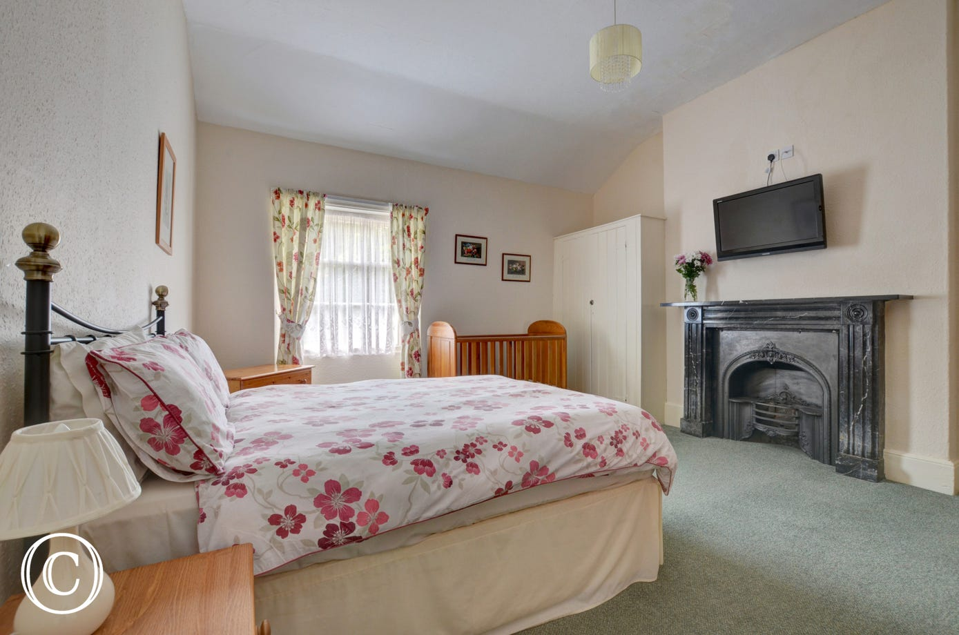 Attractive double bedroom with feature fireplace and large TV