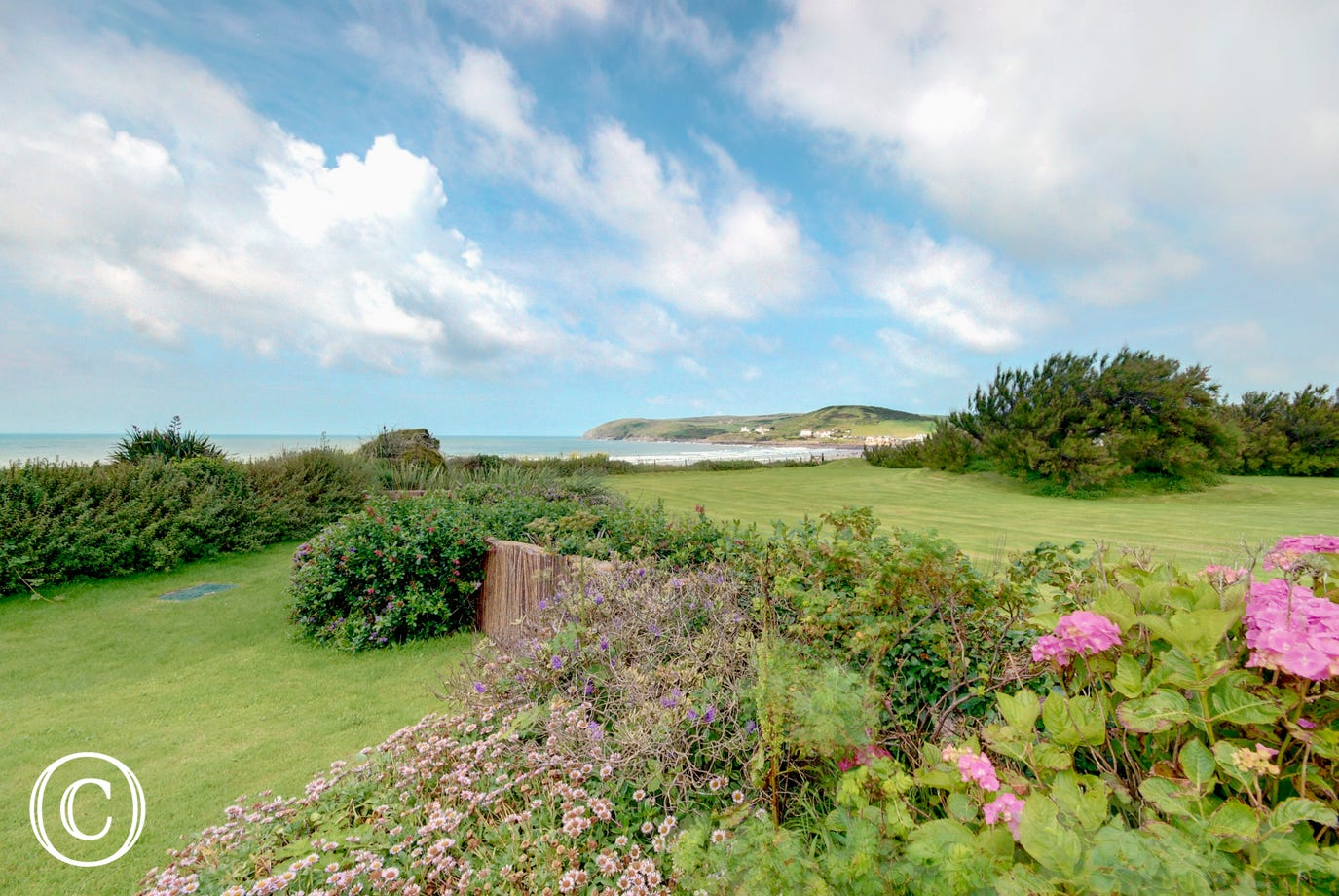 The rear lawned garden has stunning views over the beautiful sandy bay, which can be reached in minutes by a path just a few yards away