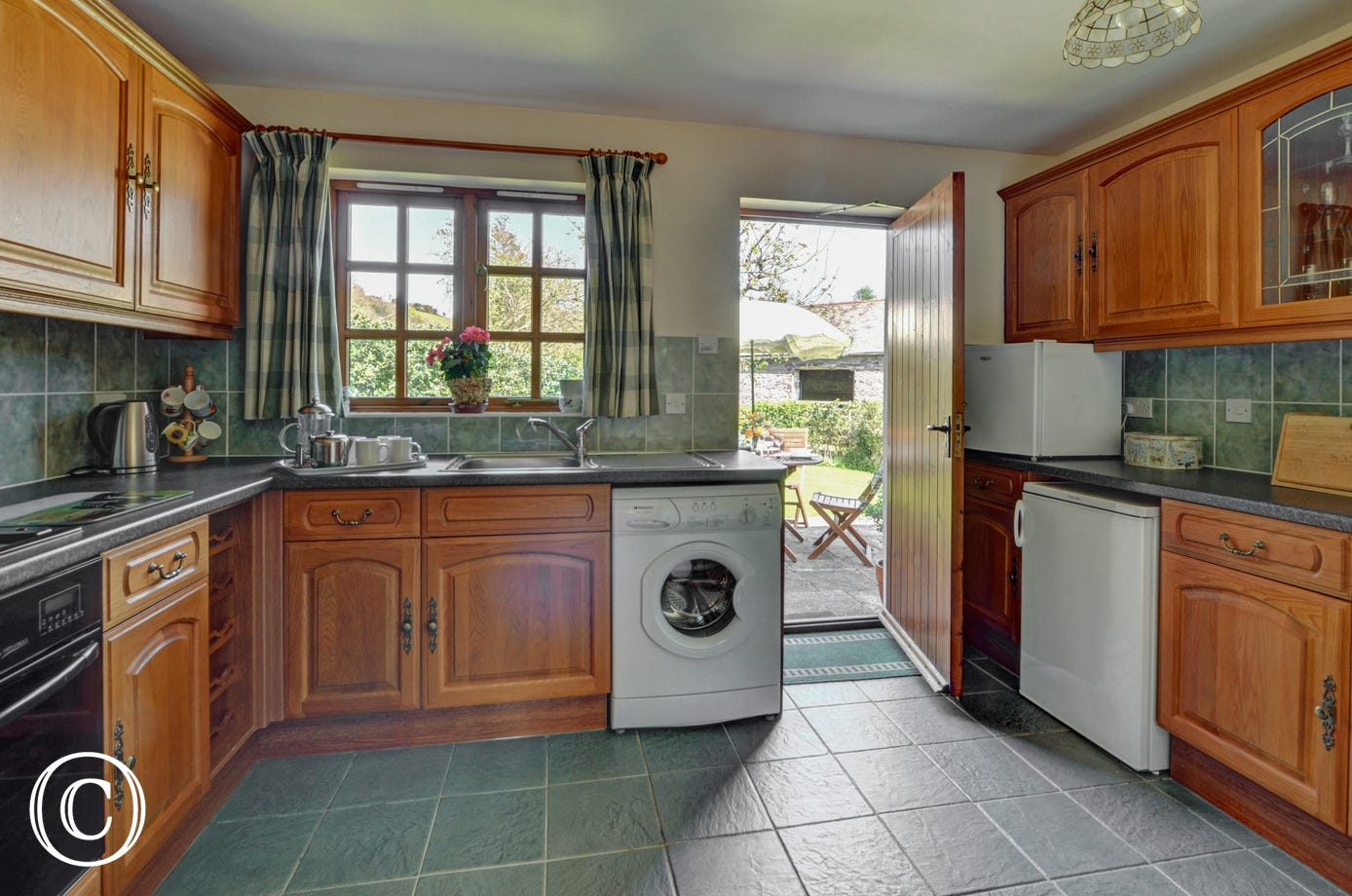 The modern fitted kitchen is well equipped and has a door leading out to the pretty garden