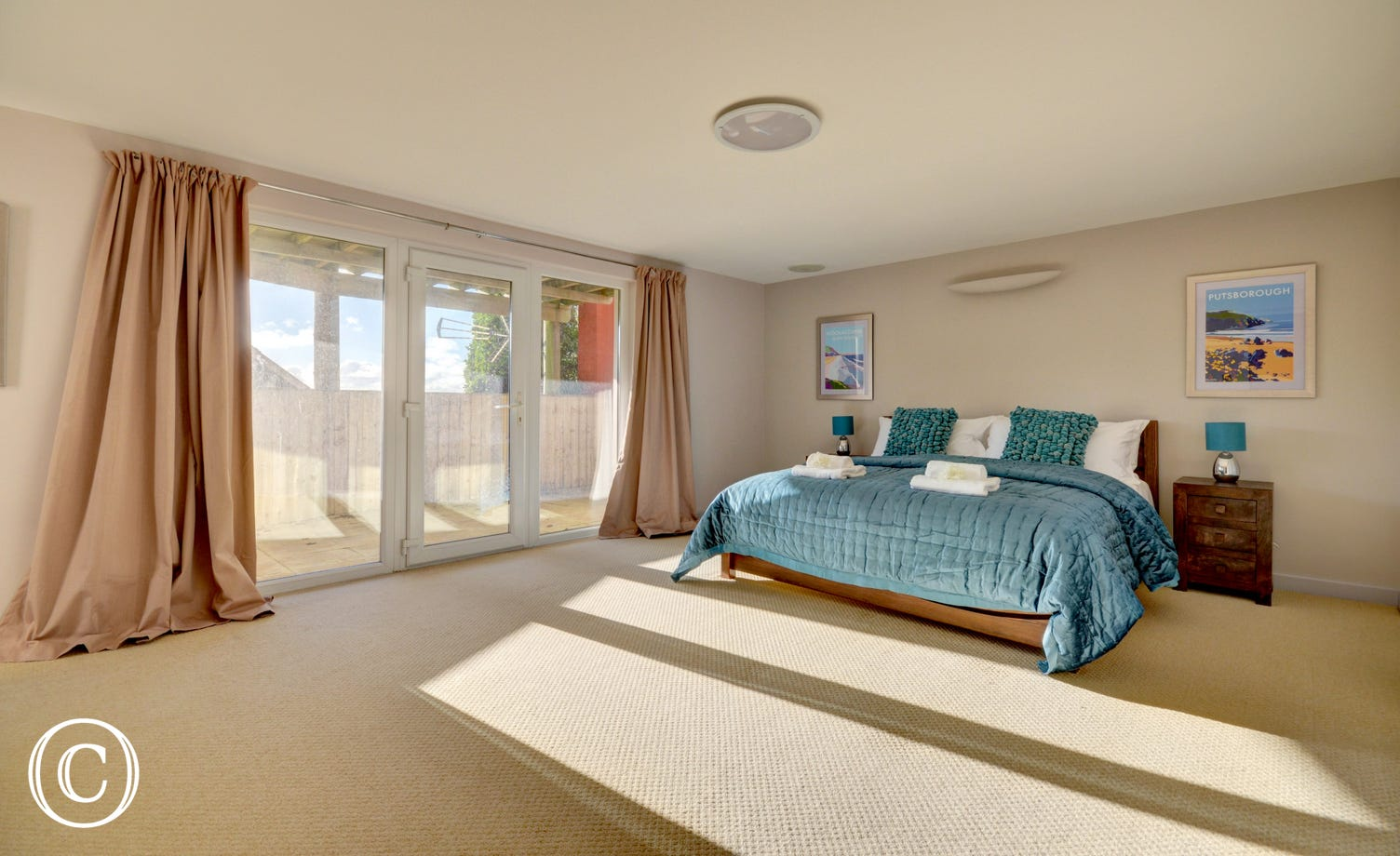 Generous size master bedroom with kingsize bed and patio doors