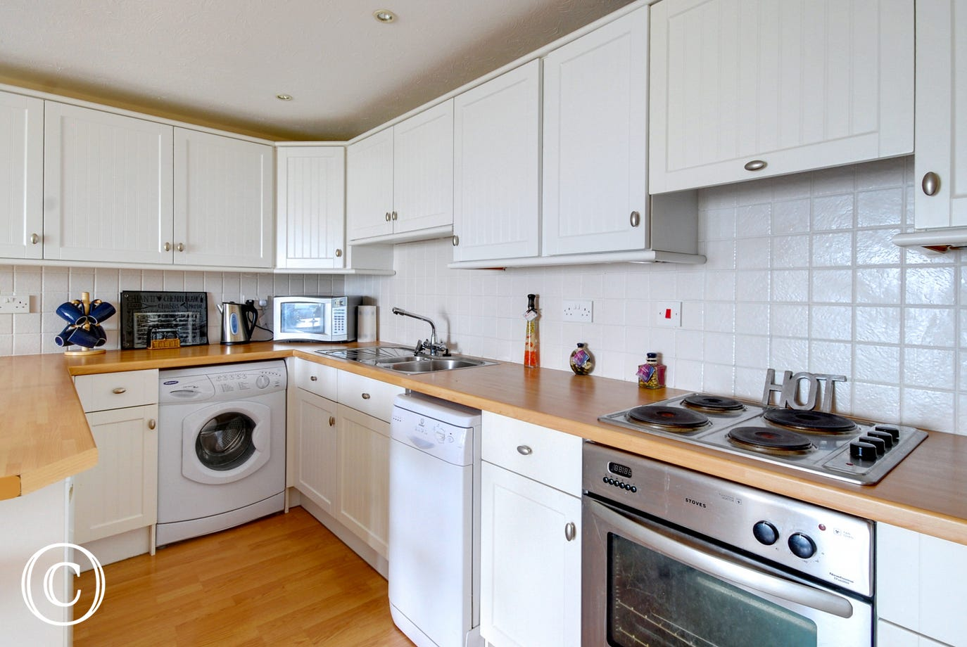 The kitchen has white units and useful breakfast bar