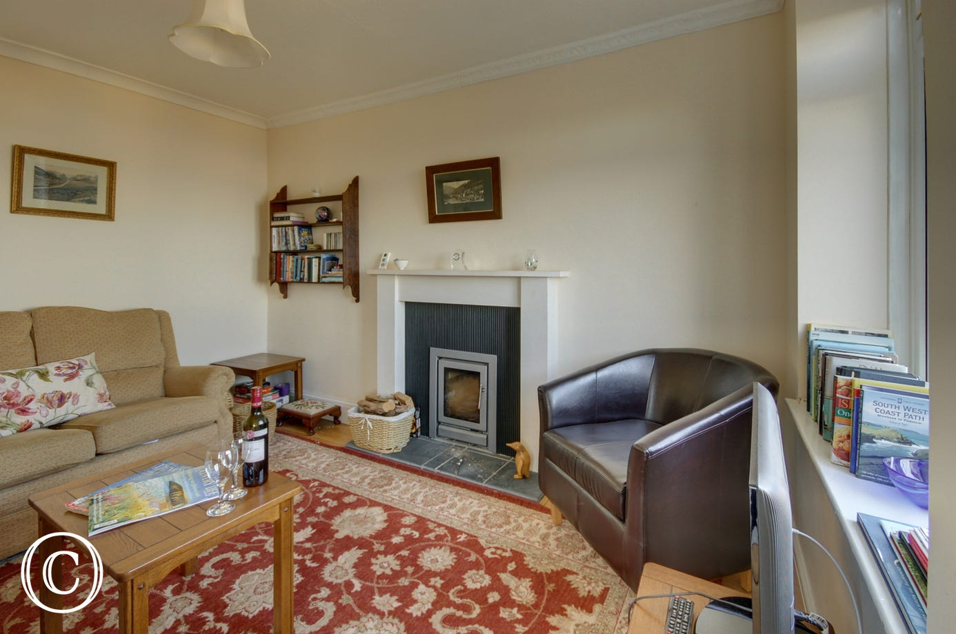 The cosy living room has underfloor heating and a wood burning stove for the cooler seasons