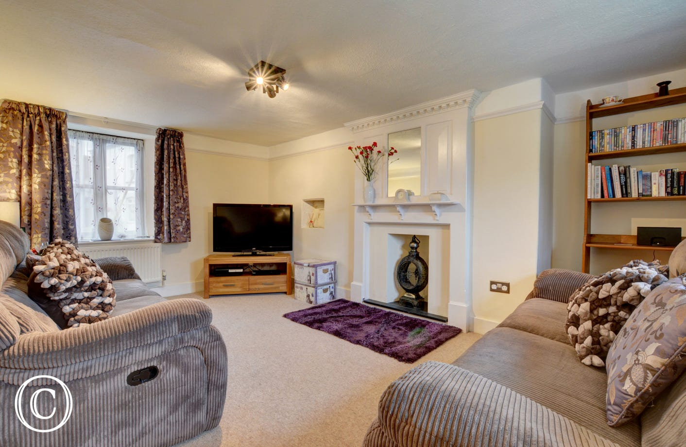 42 inch TV in the sitting with with comfy sofas and ornate fireplace