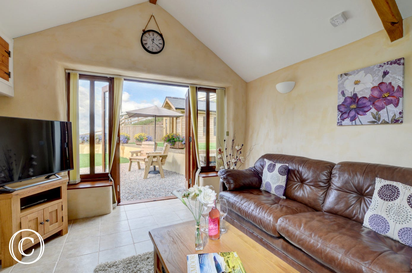Comfortable seating and large TV in the seating area, with patio doors giving access to the garden