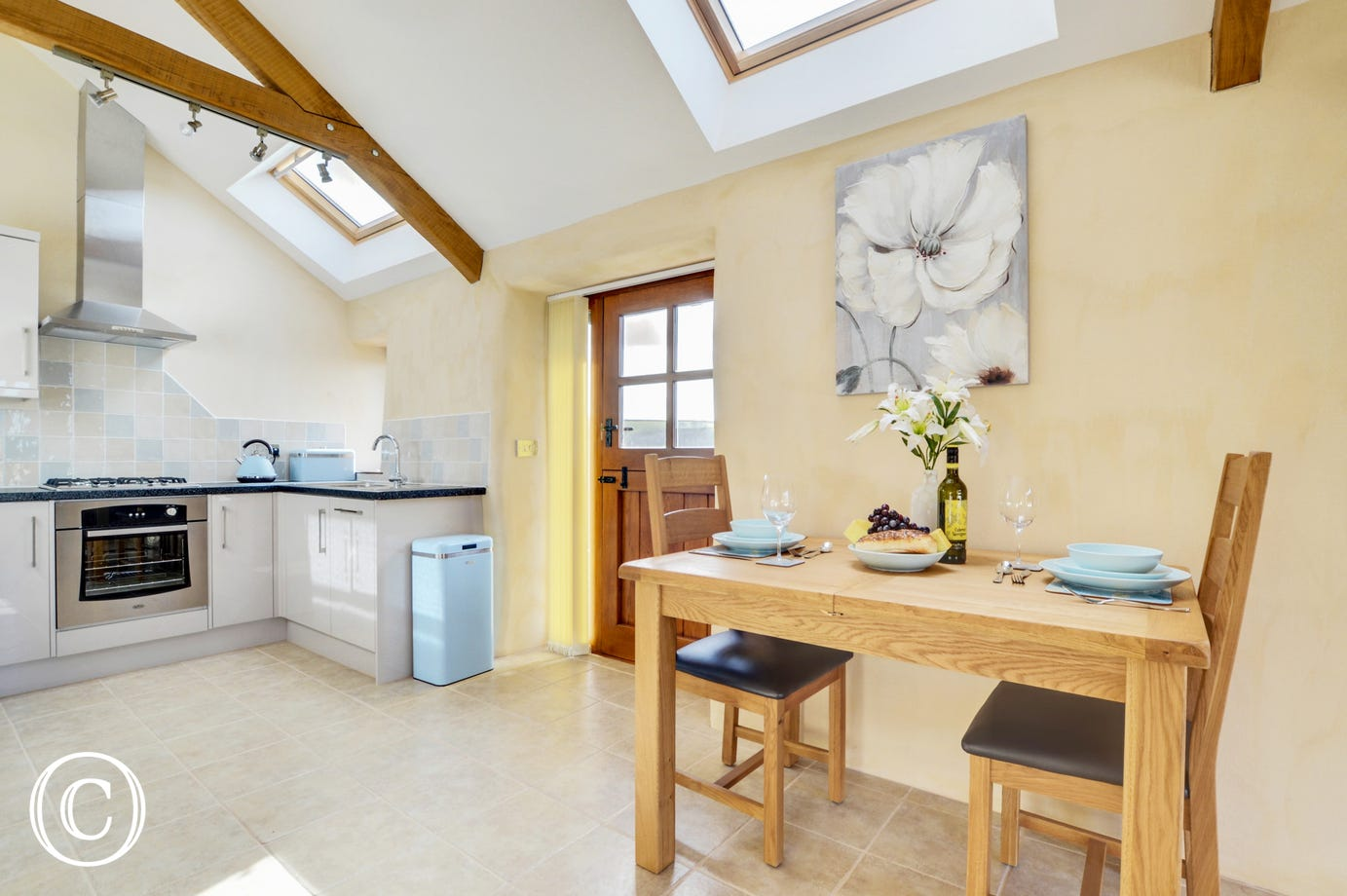 The high apex ceiling and velux windows offer a bright and spacious open plan living space