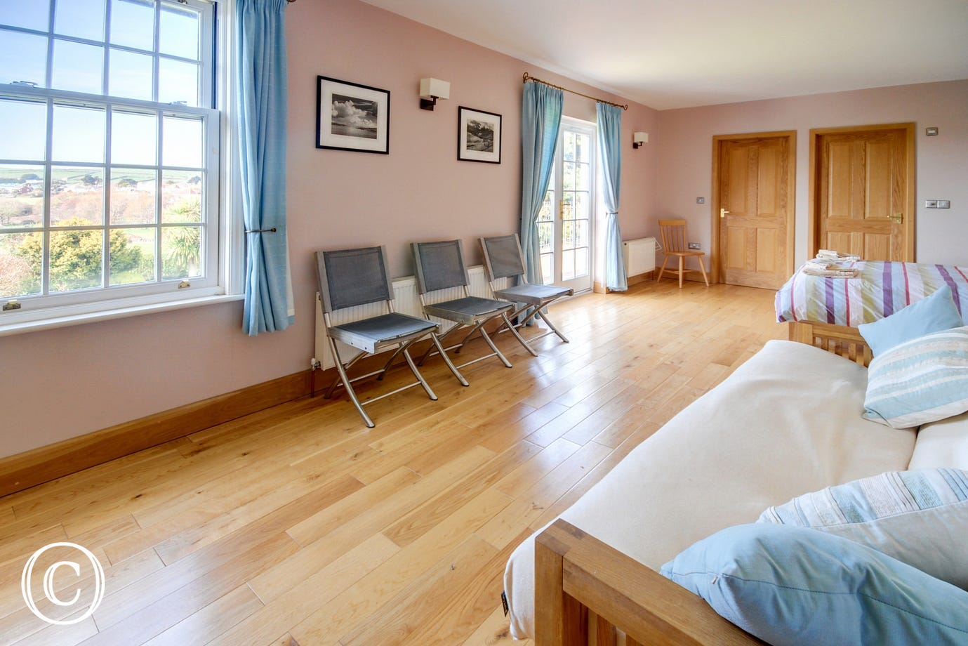 Very spacious master bedroom with wooden floors and seating