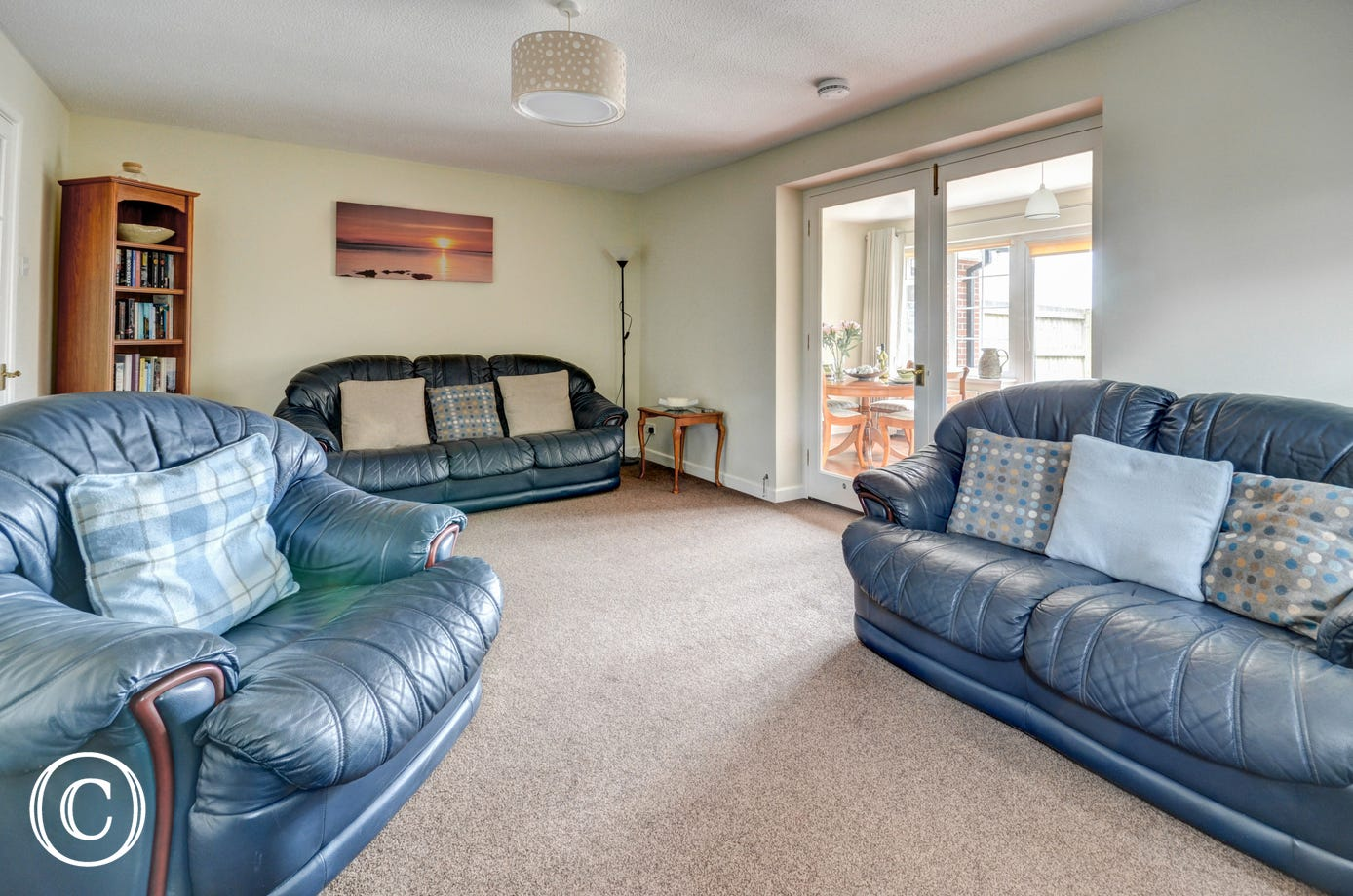 The spacious living room is very comfortably furnished and leads into a large sun lounge/dining area