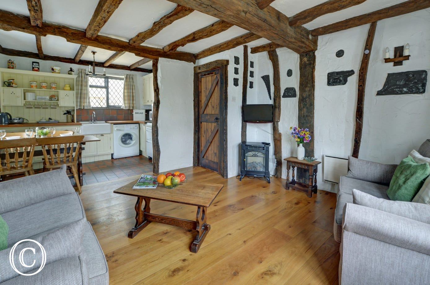 A spacious open plan living room has a dining area and attractive cottage style kitchen to one end