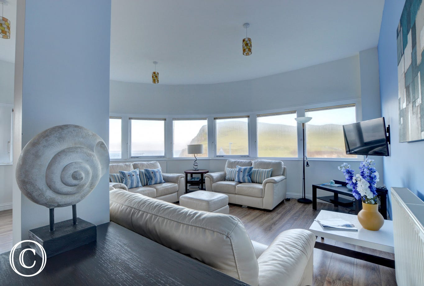 Comfortable cream leather sofas in the sitting area and spectacular views