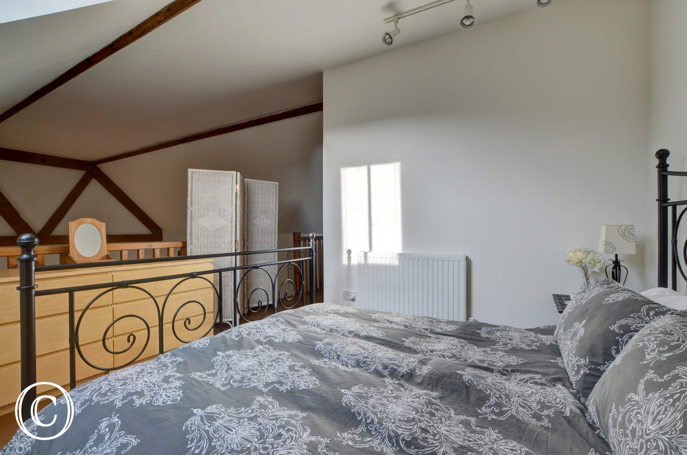 A staircase leads up to a mezzanine floor which offers a double bedroom which is open to the high vaulted ceiling and with a balustrade overlooking the living room below