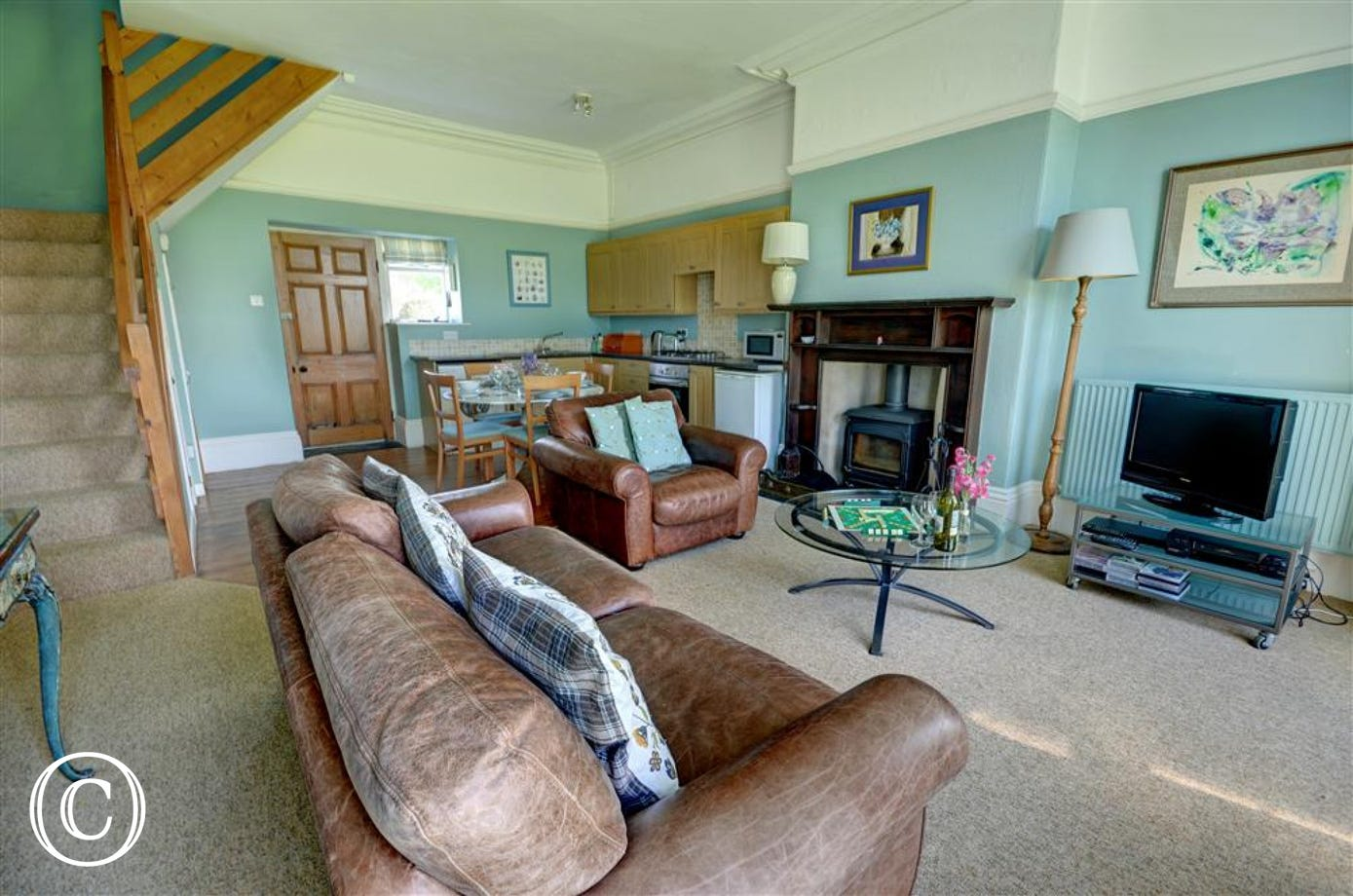 A splendid sitting room with comfy leather sofas and wood burning stove