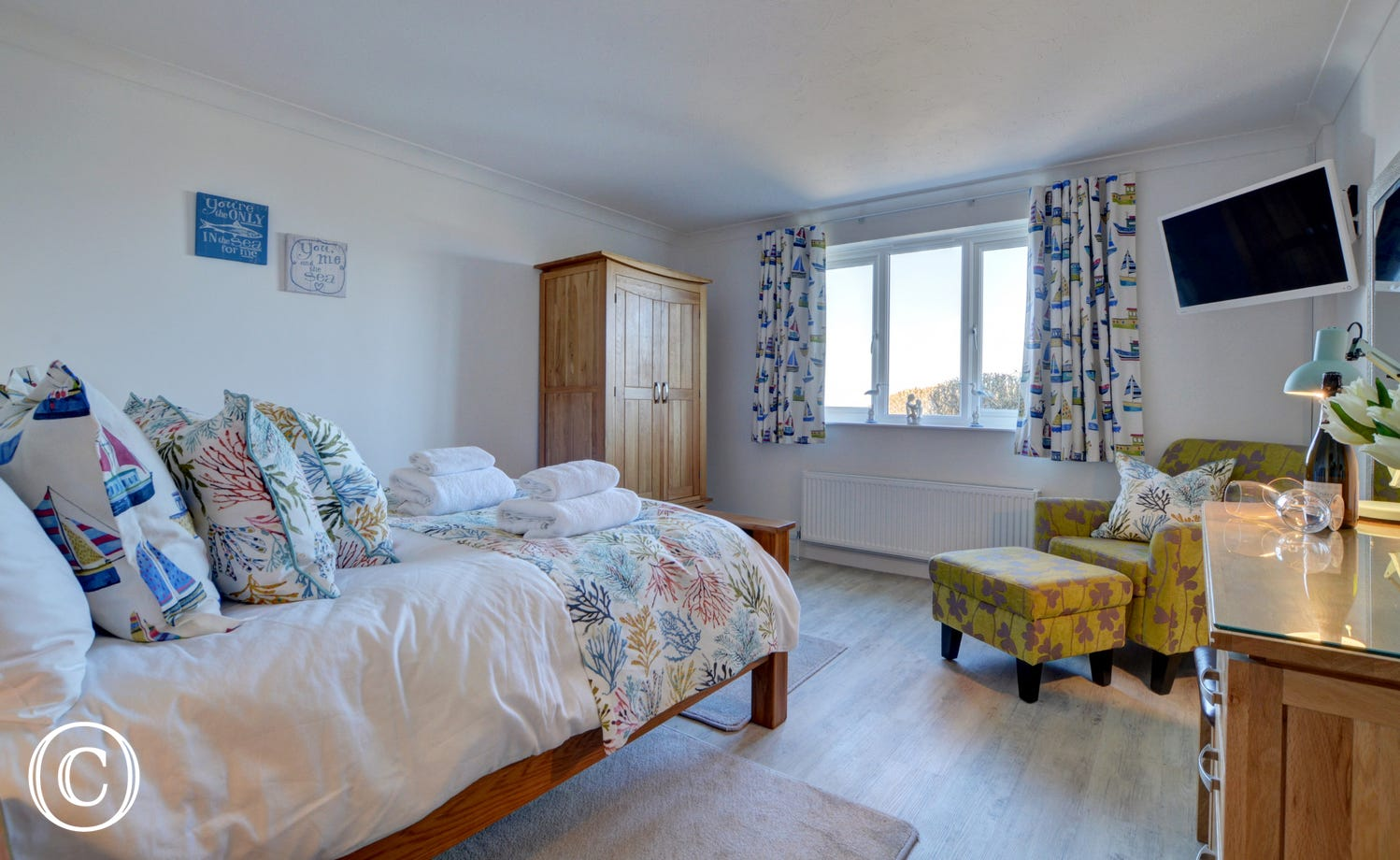 The beautifully decorated master bedroom with seating area and TV