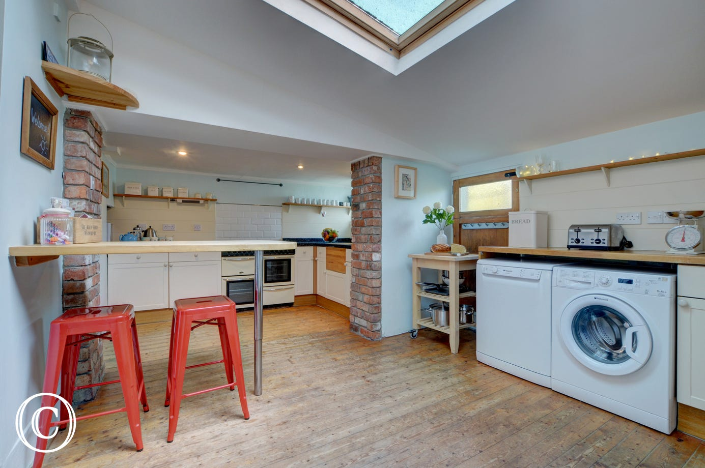 The well-equipped large kitchen with low ceiling in parts, original wooden floors, breakfast bar and large range cooker