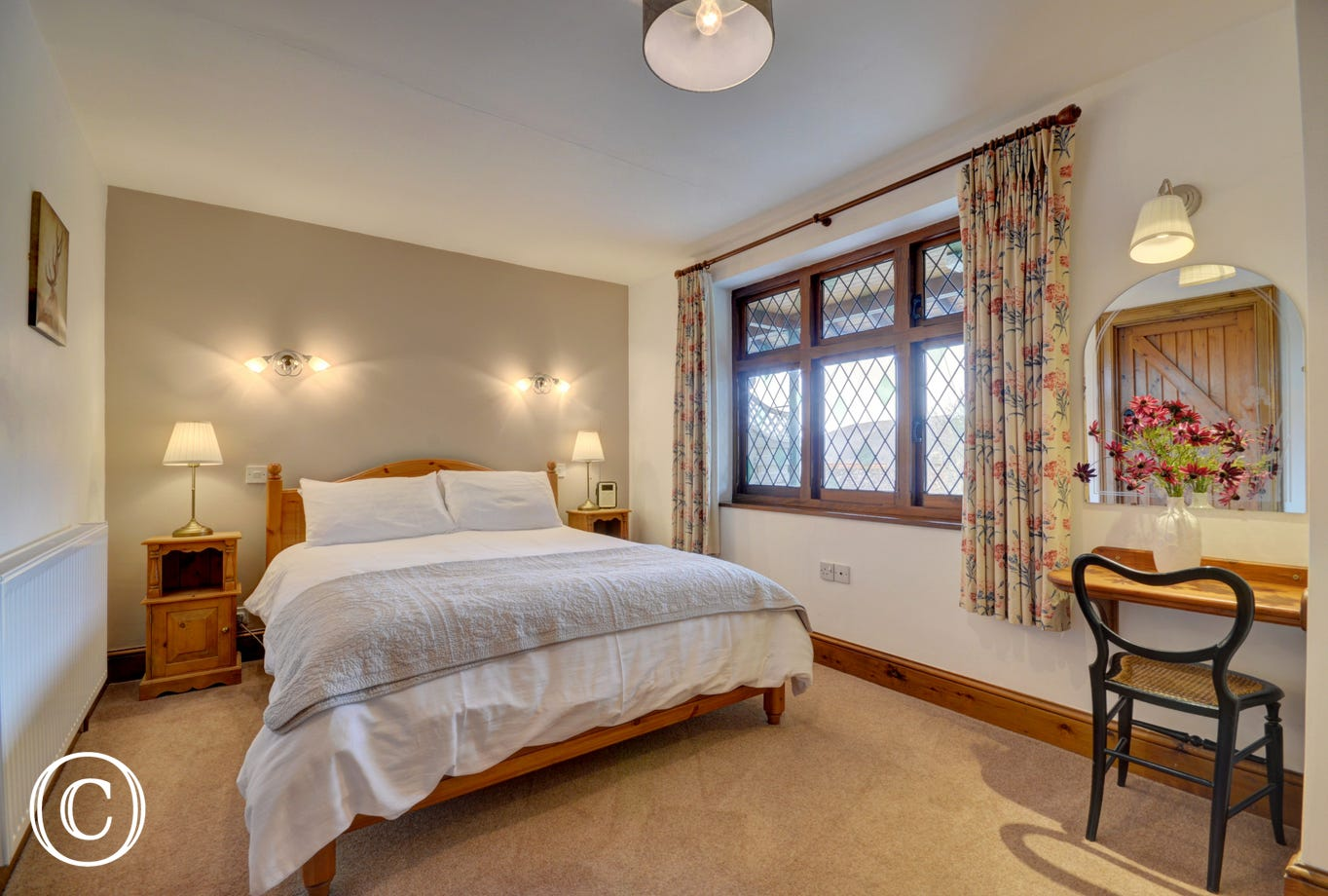 An attractive bedroom is at the front of the cottage with a Kingsize bed and a spacious ensuite bathroom with bath and walk-in shower