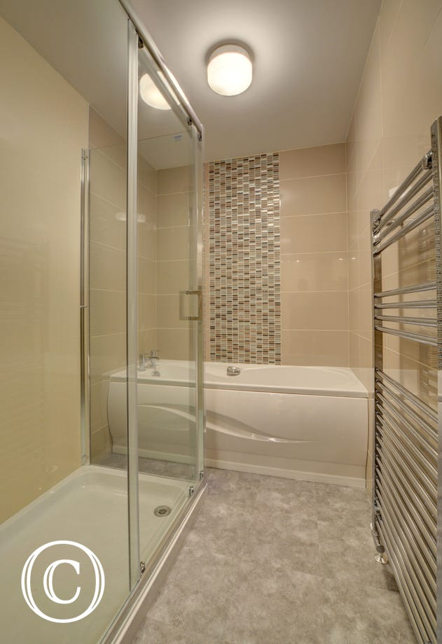 The stylish bathroom with large shower, bath and heated towel rail