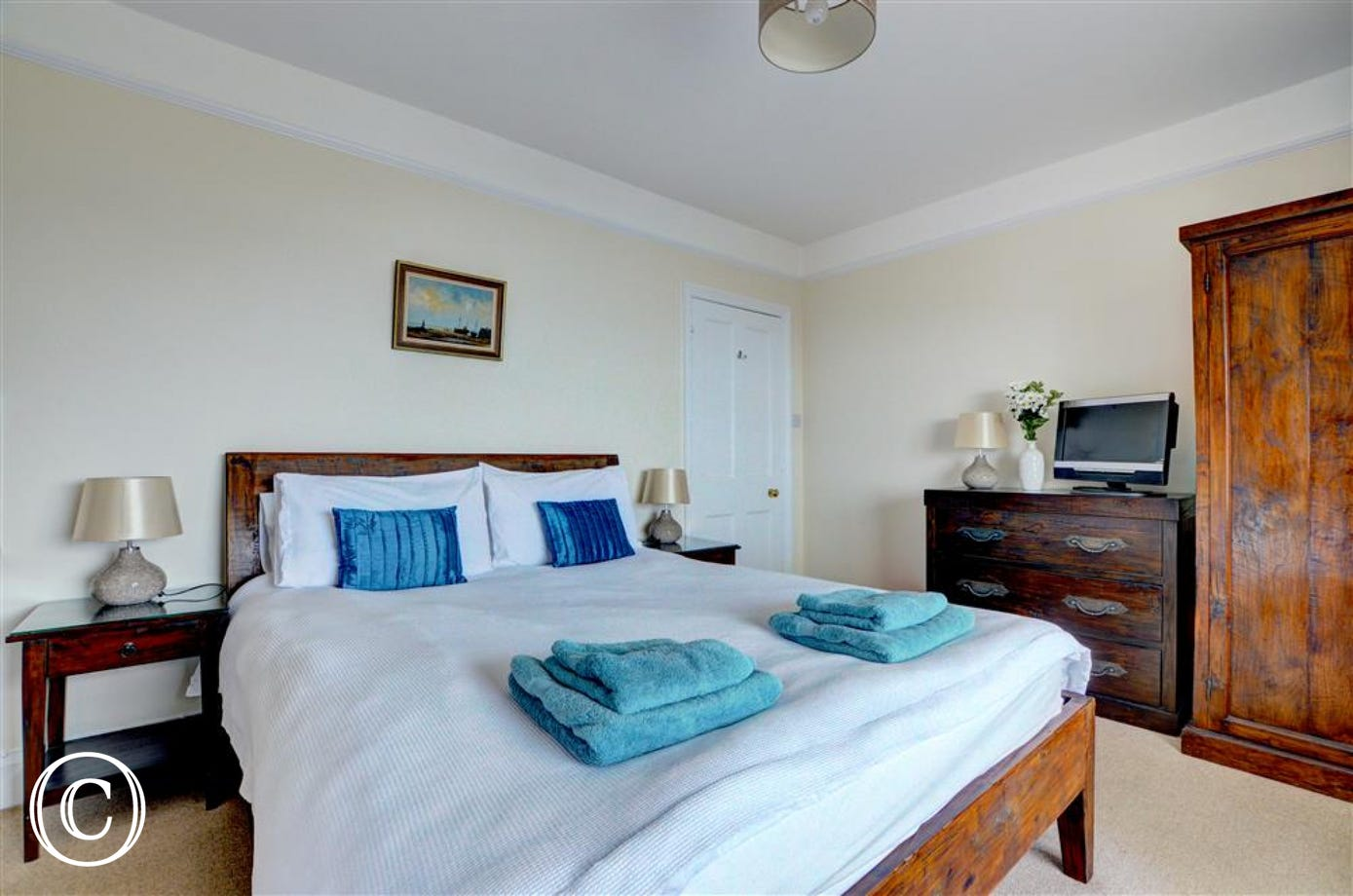 Stylishly presented master bedroom with TV and basin