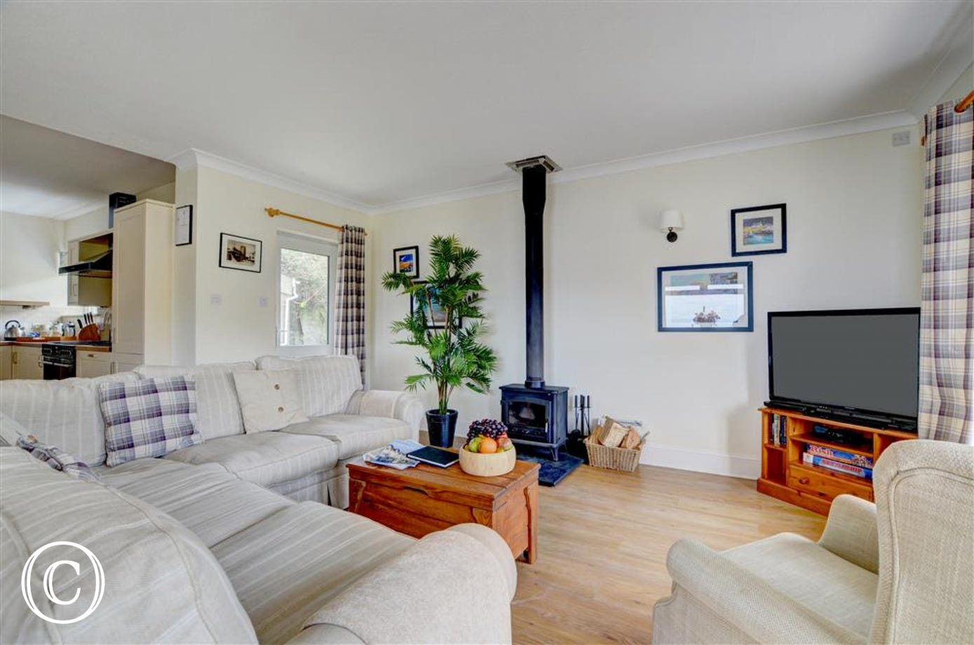 Large TV and cosy woodburner in the seating area