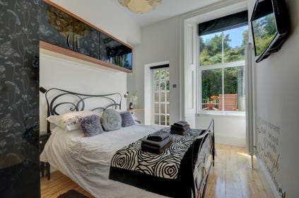 The double bedroom features a wall mounted flat screen TV and a French door out onto the rear patio