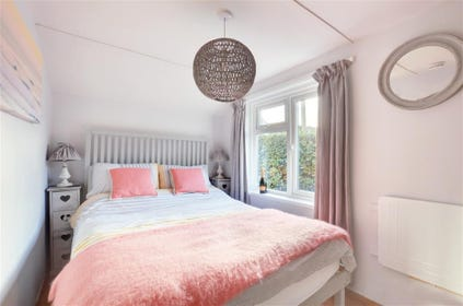 Compact double bedroom with colourful bedding