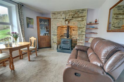 The front door opens into a cosy character living/dining room offering lovely Exmoor hillside views