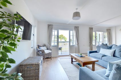 Harbour View has a very spacious and comfortable open plan living area with two French windows leading out onto a full length canopied balcony
