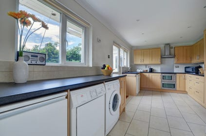 Spacious modern kitchen furnished with light oak units and granite style worktop