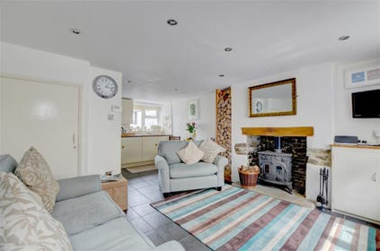 The stylish open plan living room features a cosy wood burning stove, a real treat on cooler evenings