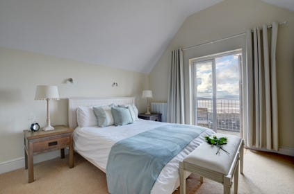 On the first floor the master bedroom furnished in a fresh New England style and with an ensuite wet room