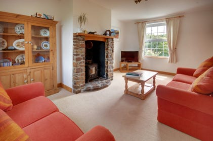 The living room benefits from a wood burning stove set in an attractive stone fireplace, surrounded by two terracotta coloured sofas
