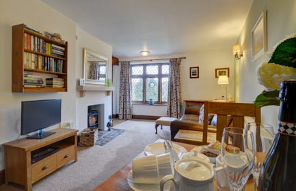 The open plan very comfortable living/dining room with woodburner in feature fireplace ideal for cosy evenings in